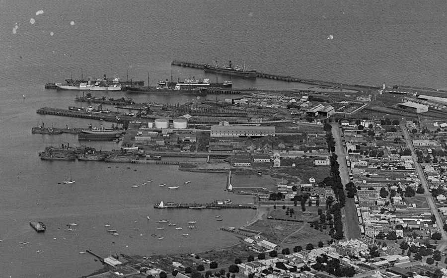 A black and white aerial photograph of a dockyard. The dockyard is made up of several buildings, piers and ships.