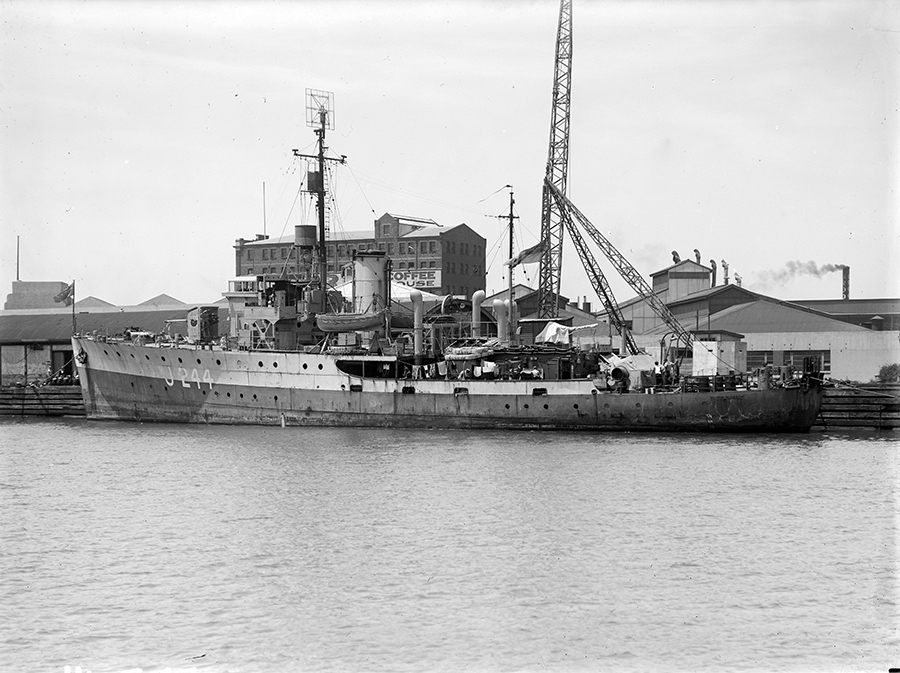 A black and white photograph of a military ship anchored at a jetty. Industrial buildings can be seen in the background.
