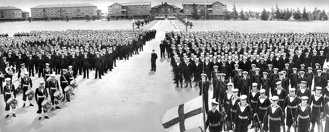A black and white photograph of a large group of military personnel stand in formation in a parade ground.