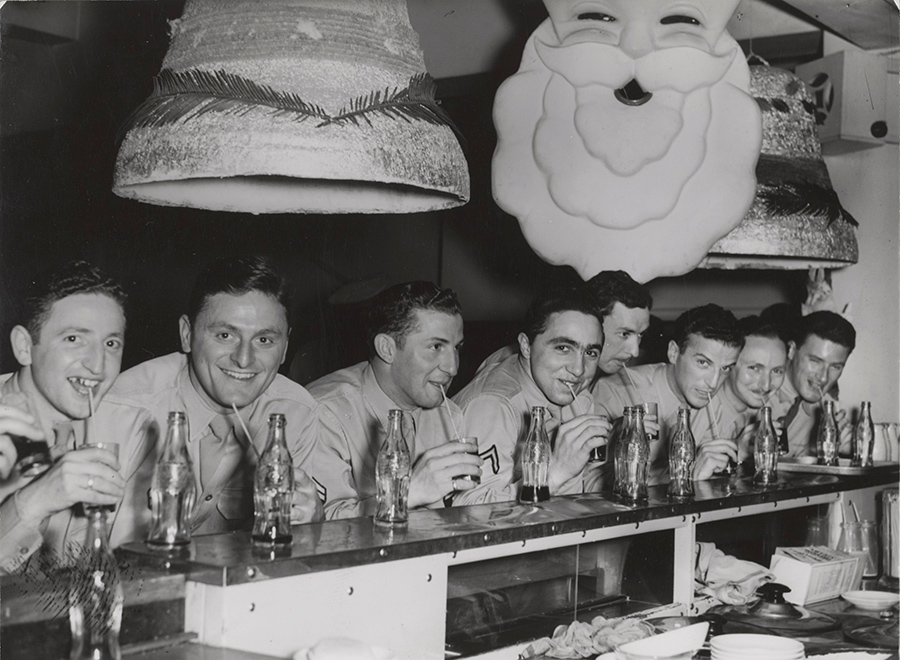 A black and white photograph of a group of men stand at a bench drinking bottles of softdrink. Christmas decorations are hung above the men.