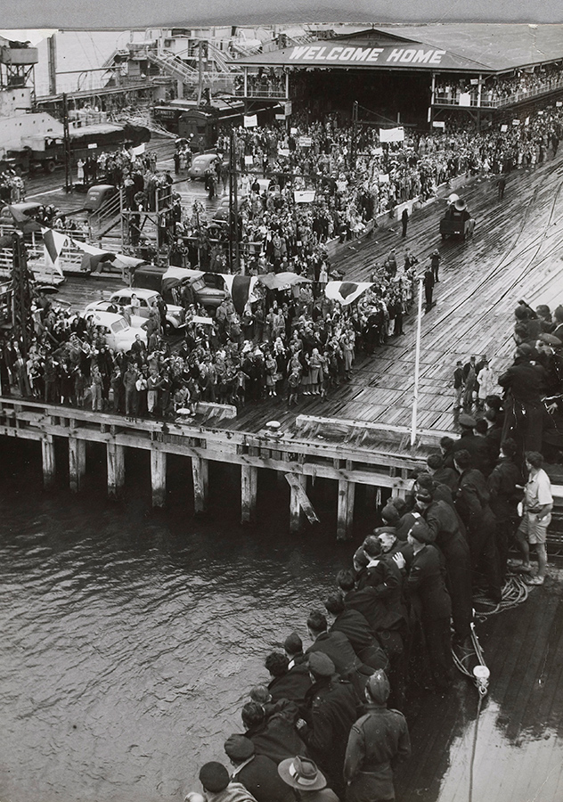 A black and white aerial photograph of a large crowd gathered on a pier. The words welcome home are written on the awning of a building.