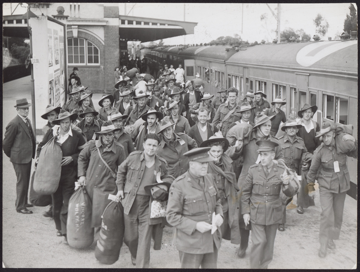 A black and white photograph of a group of uniformed men disembarking from a train. Many of the men are carrying rucksacks.