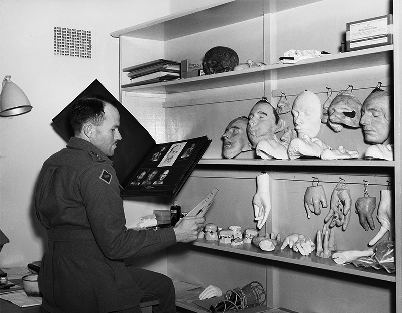 A black and white photograph of a man in uniform holding a folder with a series of men's headshots visible. In front of him are shelves with various prosthetic hands and faces.