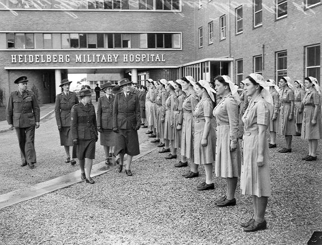 A black and white photograph of multiple rows of uniformed women nurses stand in a courtyard of a multi storey building as a group of four women and a man in military uniform walk past. The words Heidelberg Military Hospital can be seen on the building's wall.