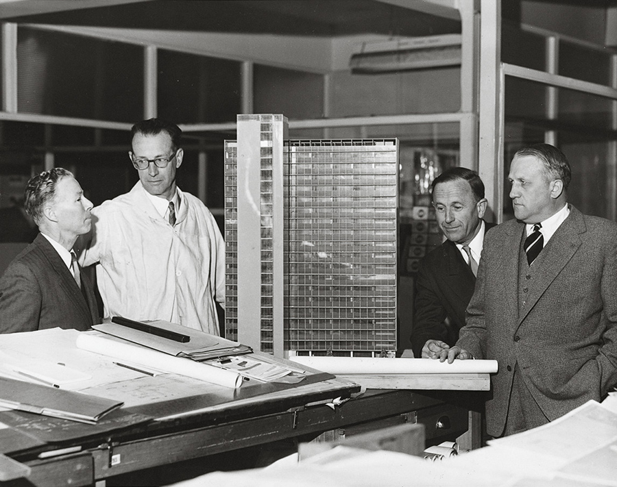 A black and white photograph of four men in suits sanding around a model of a skyscraper. In the foreground is a table covered in architectural drawings.