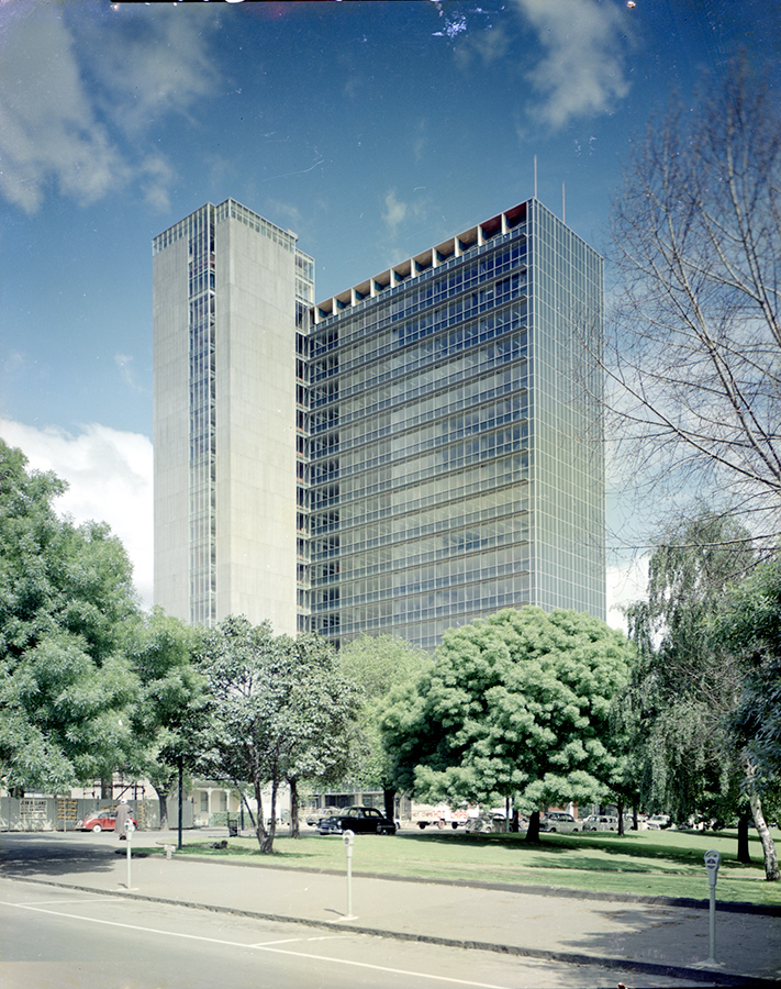 A colour photograph of a glass skyscraper. There are several trees in the foreground showing the enormous scale of the building.