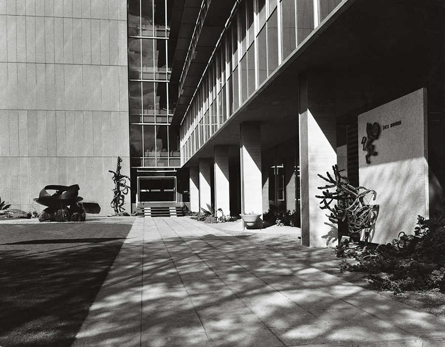 A black and white photograph of an entrance to a modernist building. To the left of the doorway is a modern style steel fountain that is an abstract circular shape.