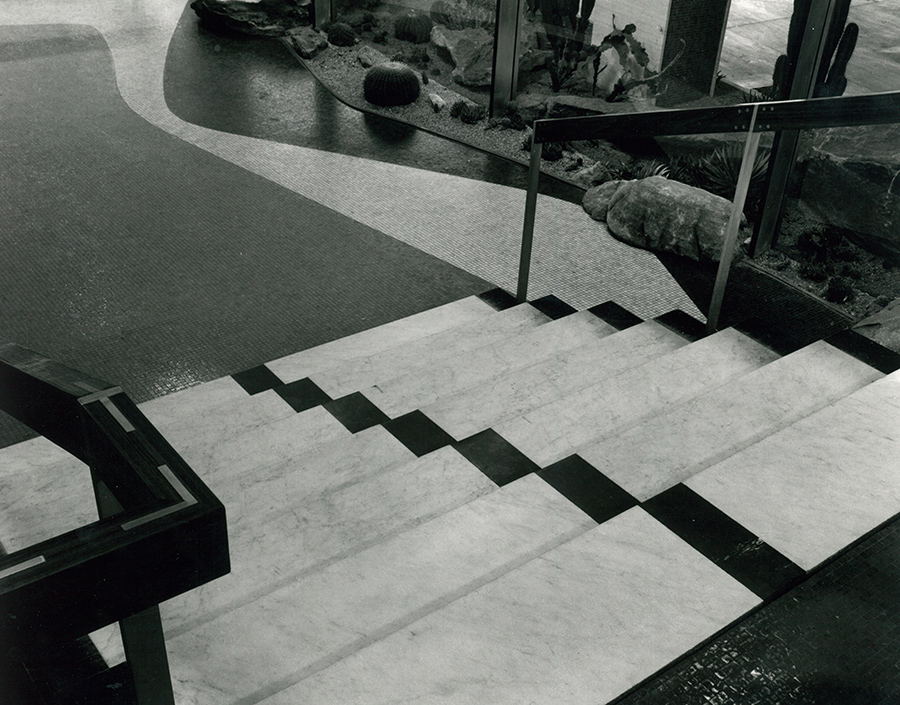 A black and white photograph looking down a marble staircase. The marble of the floor and staircase is designed in a minimalist pattern of contrasting shades. Next to the staircase is a window and a small manicured garden can be seen on the other side.