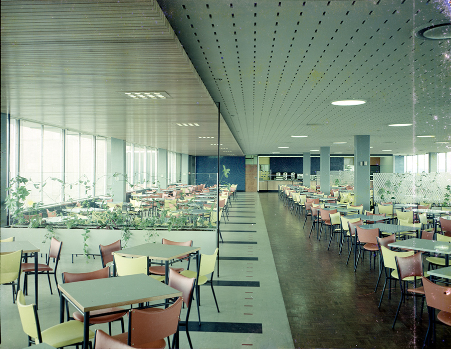 A colour photograph of a large cafeteria made up of numerous sets of tables, each surrounded by four chairs.