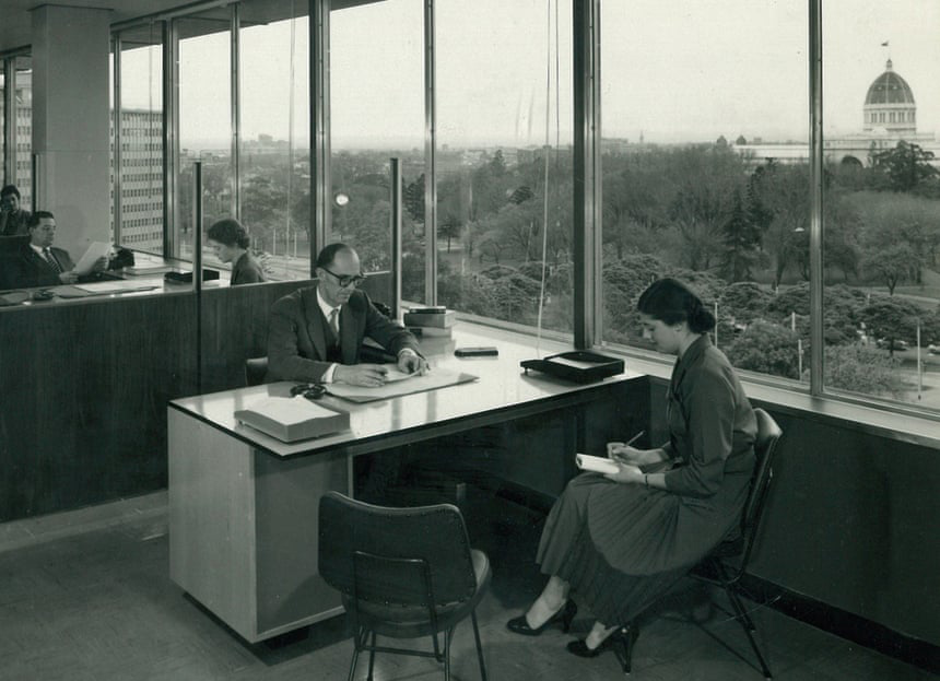 A black and white photograph of a man and woman sitting at an office desk next to a large glass window. Through the window is a park and the top of the dome of the Melbourne Royal Exhibition Building can be seen in the distance.