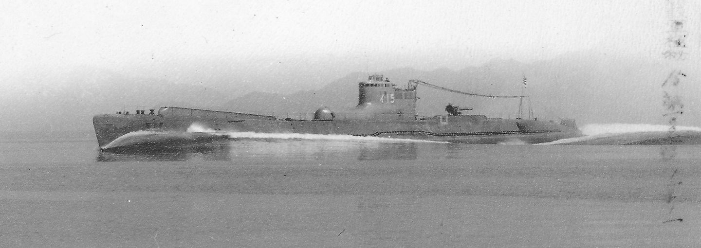A faded black and white photograph of a Japanese submarine breaching the surface of the water. A misty mountain range can be seen in the background and there is faded Japanese text printed on the side of the image.