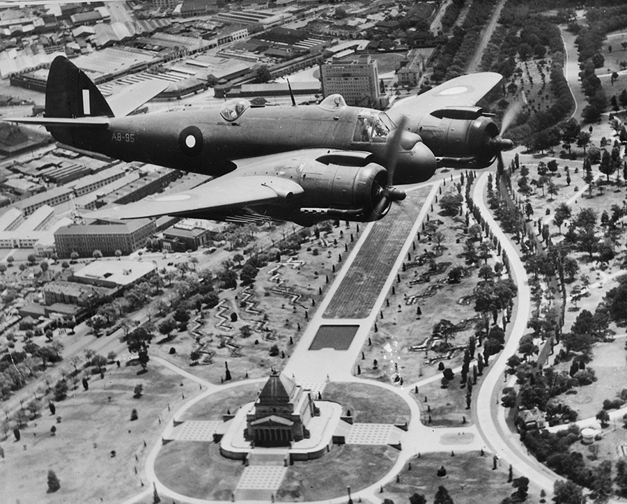 An aerial black and white image of a World War Two fighter plane flying over a city. A manicured garden with zigzagging trenches and a large classical style building can be seen below the plane.