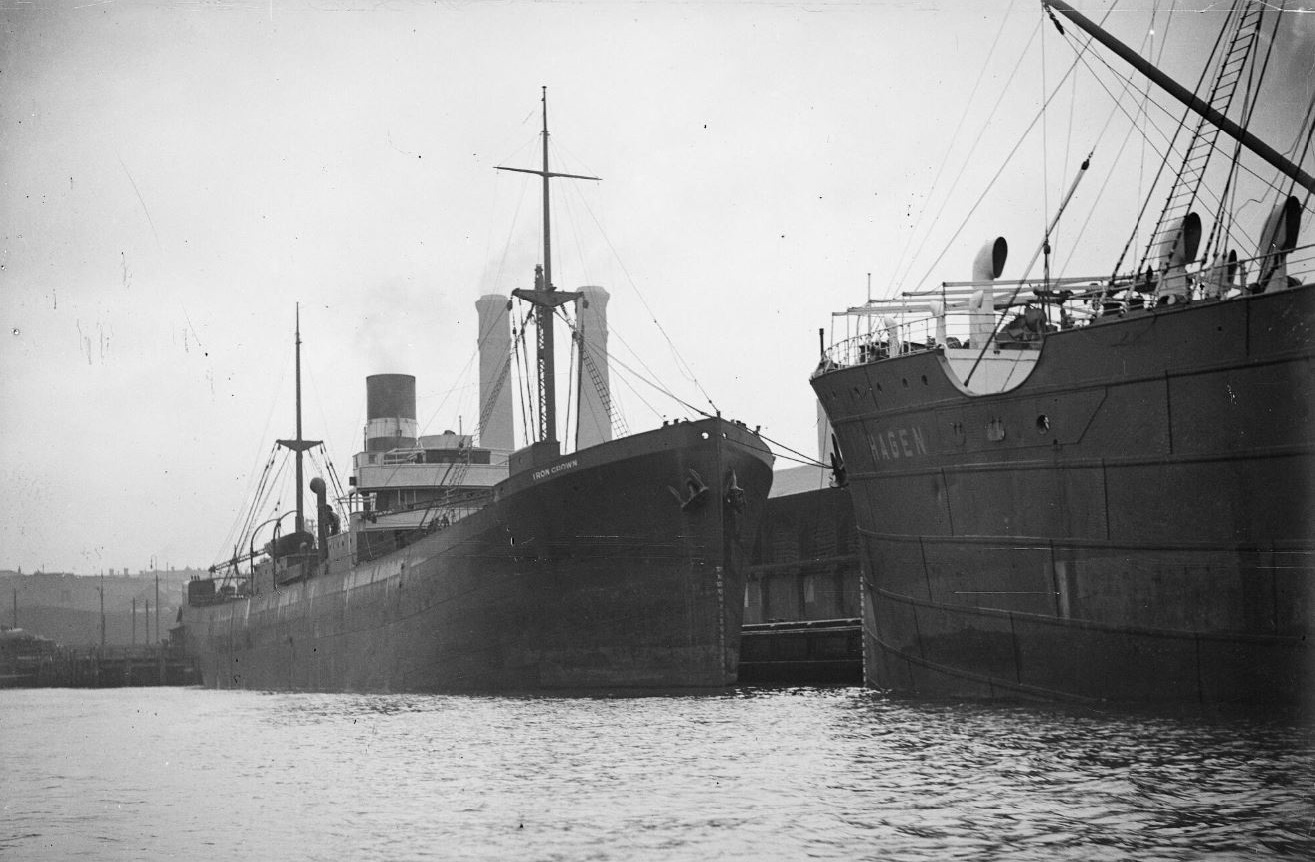 A black and white photograph of two large ships anchored at a jetty.