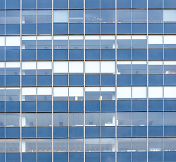 A colour photograph of rows of office windows. The composition of the image is a grid and there is a blue hue to the photograph.
