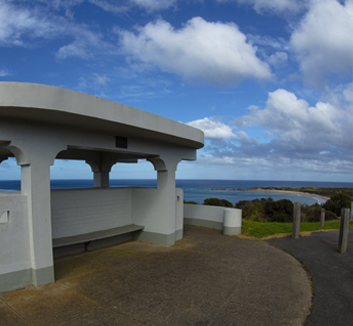 A colourful image of a concrete lookout and car park sitting on top of a hill overlooking a lush Australian coastline.