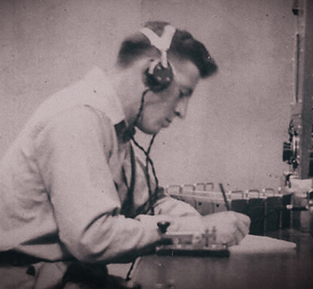A grainy black and white photograph of a young radio operator focused on a pen and pad. He sits at a bench in front of morse code and radio equipment.