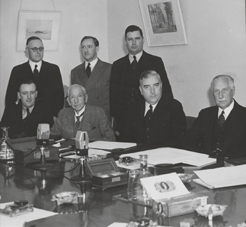 A black and white photograph of six men in suits sitting on a row on at a wooden table with three men standing behind them. The table is covered with paper documents and two microphones can be seen.