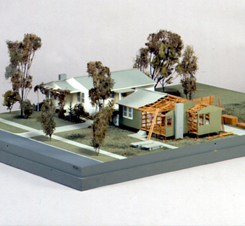 A colour photograph of a model of a single storey house with a gabled roof. Part of the house is shown exposing the timber frame.