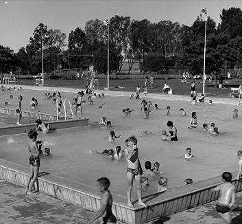 A black and white photograph of an outdoor Olympic swimming pool. Several groups of children can be seen playing in and around the pool. A small boy stands in the foreground giving a thumbs up to the camera.