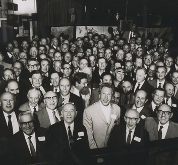A black and white photograph of a large group of men standing in a hall. The men are smiling and wearing suits.