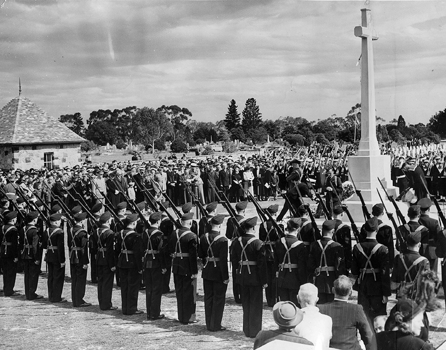 A black and white photograph of a ceremony taking place in front of a large stone crucifix. Two rows of military personnel can be seen in the foreground holding rifles.