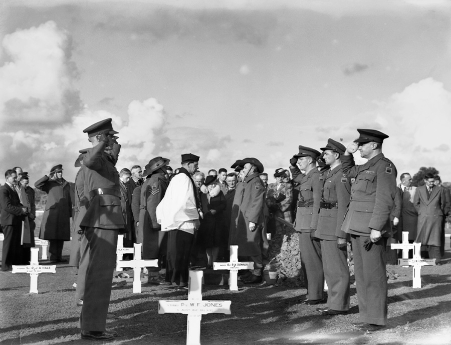 A black and white photograph of men in military uniforms standing in a cemetery. The group face each other and are saluting. There is a group of onlookers in the background.